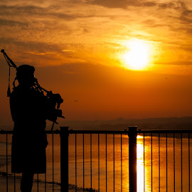 Bagpiper Playing On a Bridge At Sunrise by Dave Sheffield - People Street & Candids ( bagpipe on bridge over river, musical candids, bagpiper silhouette at sunrise, quad cities marathon 2014, bagpipes at sunrise )