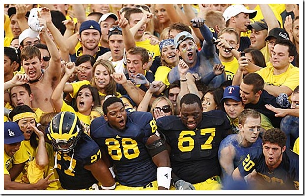 (caption) Michigan safety Brandon Harrison (27), defensive end Andre Criswell (88) and defensive tackle Terrance Taylor (67) join the fans in the Michigan student section to celebrate their come-from-behind victory. *** Michigan rallies back from a 19-0 deficit to stun the ninth-ranked Wisconsin Badgers 27-25, giving new head coach Rich Rodriguez a victory in his first Big Ten game. *** The Michigan Wolverines (1-2) host the 9th-ranked Wisconsin Badgers in U-M head coach Rich Rodriguez' first Big Ten game. Photos taken on Saturday, September 27, 2008.  ( John T. Greilick / The Detroit News )