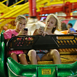 Friends Texting by Jerry Ehlers - City,  Street & Park  Amusement Parks ( girls, texting, amusement park, amusement ride )