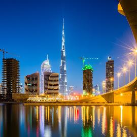 Dubai skyline 1 by Cesar Crusat - City,  Street & Park  Skylines ( emirates, reflection, skyline, cityscape, travel, business, towers, city view, dubai, puente, long exposure, nikon, downtown, helicopter, office, building, larga exposicion, vivid colors, lake, skycrapers, burj khalifa, lago, d7100, uae, bridge, travel photography )