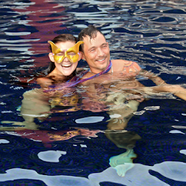 In the Pool by Venetia Featherstone-Witty - People Couples ( water, girl in mask, reflections, couple, couple in pool, people )