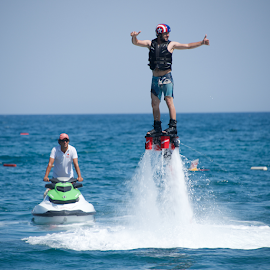 Flyboarder giving thumbs up beside jet ski by Nick Dale - Sports & Fitness Watersports ( spray, water sports, jet ski, mediterranean, sea, flyboarding, turkey, bodrum, helmet, man )