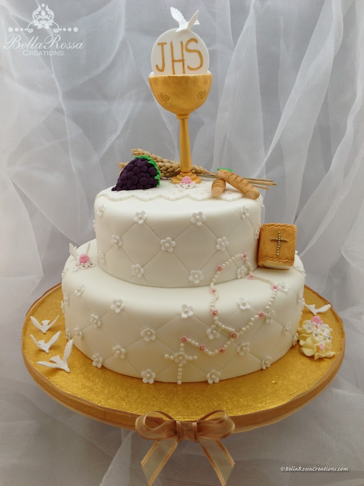 2-tier vanilla sponge cake for a little girl first communion complete with edible golden chalice, bunch of grapes, bread and golden bible. This cake also had a sugar pearls rosary on the bottom tier.