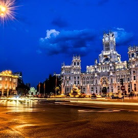 Madrid Palace of Communications by Justin Murazzo - City,  Street & Park  Street Scenes ( palacio de comunicaciones, old, gateway, street, stone, busy, yellow, spain, city, contrast, sky, hurry, buildings, paseo del prado, light, orange, asphalt, twilight, white, tourism, windows, concrete, calle de alcala, traffic, headlights, fountain, trees, palace, calle, car, communications, madrid, quick, beauty, blur, road, plaza de cibeles, paseo de recoletos, taillights, evening, lit, hdr, streetlight, speed, beautiful, scenic, high dynamic range, main, blue, sunset, clarity, night, scenery )