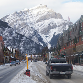 Banff Avenue by Mick Cook - City,  Street & Park  Street Scenes ( clouds, mountains, street, snow, buildings )