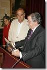 El alcalde, a la derecha, da lectura a la leyenda de la placa entregada al policía jubilado, en presencia de su esposa.