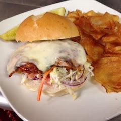 Jerk chicken sandwich- Caribbean slaw, cheddar cheese, house made chips.