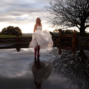 A wet wedding, Bride in Wellington boots. by Tommy  Cochrane - Wedding Bride ( wedding, puddle, wellington, wet, bride, rain, boots, reflection. )