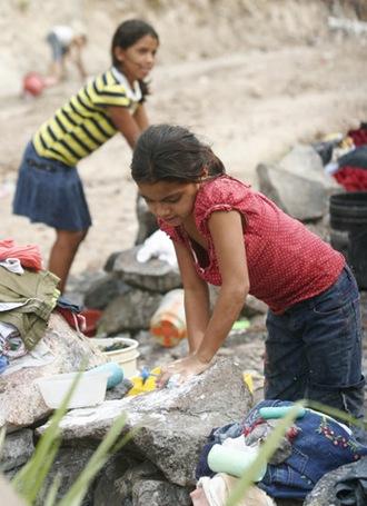 Niñas residentes en la comunidad El Cañito, cercad e la colonia Costa Rica lavan su ropa ayudando de esta forma en las labores de sus hogares. El trabajo infantil es una de las peores formas de explotación en América Latina. Foto de LA PRENSA.