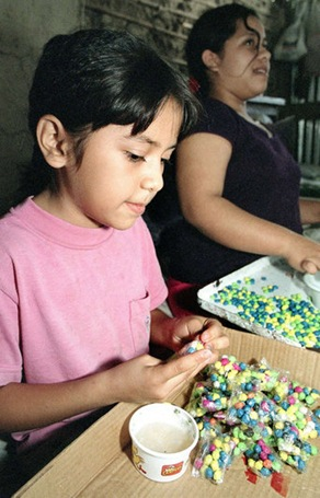Susana Aracely Ramírez, de 8 años, junto a su prima Patricia, de 16 años, trabajan en la elaboración de fulminantes en la cohetería de la familia.  FOTO DE LA PRENSA