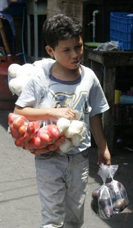 Un menor camina por el centro de  San Salvador para vender tomates, cebollas y aguacates para obtener un ingreso económico y ayudar en su casa. Foto de La Prensa, Tulio Galdámez