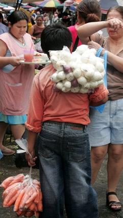 Un menor ofrece verduras a los compradores del mercado central. Con el dinero de la venta  el niño colabora con el sustento de su familia. El próximo 12 de junio se celebra el día contra el trabajo infantil. Foto de La Prensa, Mercedes Arias