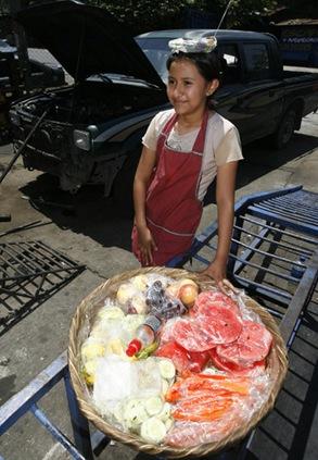 Guadalupe Noemí Guzmán Vásquez, de 11 años, ofrece fruta en un taller de Mejicanos. La niña es residente de Ciudad Futura en Mariona y ayuda a su madre con el negocio para el sustento de toda la familia. Foto de La Prensa, Víctor Peña