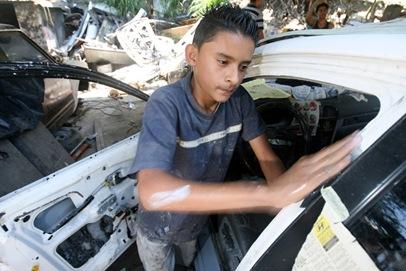 Eduardo Tobar, de 13 años,  trabaja de aprendiz en un taller de enderezado y pintura en Mejicanos. El joven estudia séptimo grado en el Centro Escolar 22 de Junio. Foto de La Prensa, Milton Flores