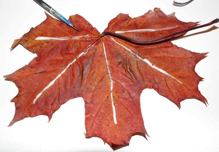 applying glue to a leaf for a leaf garland