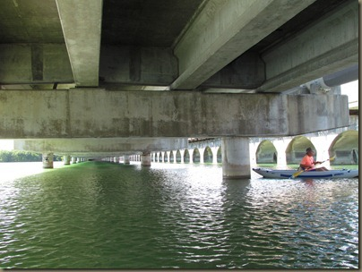 al kayaking under bridge