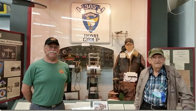 Roland Douglas, veteran of WWII, stands in front of the display about his experience as a gunner and a POW.