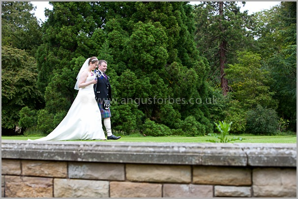 bride and groom walking round the gardens of carberry tower