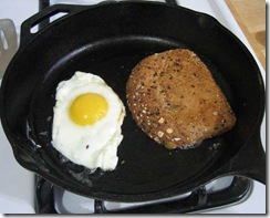 eggs and toast cooking in cast iron frying pan