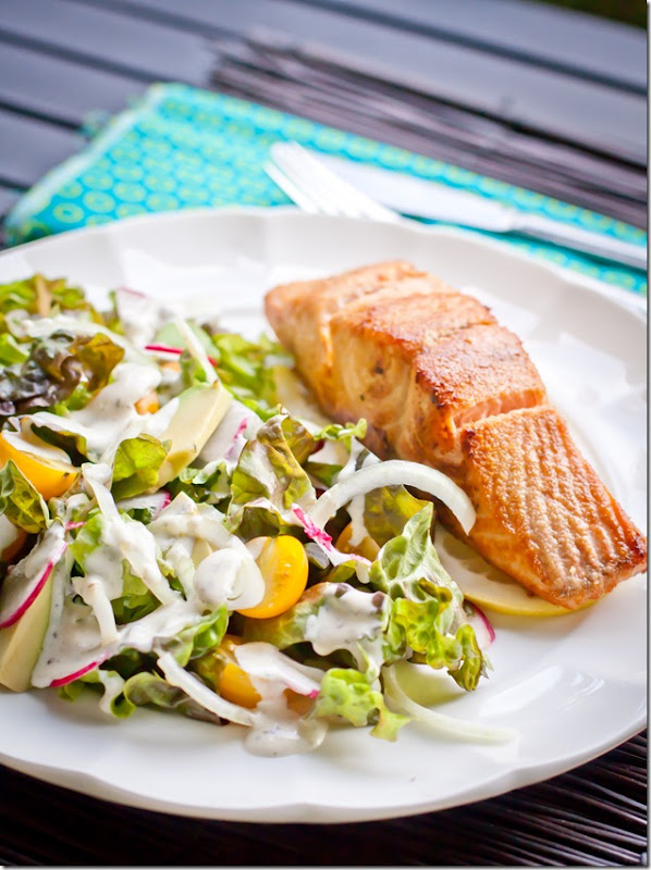 Summer salad with homemade buttermilk dressing and salmon on a white decorative plate.