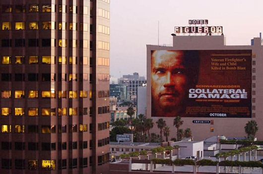 "A movie billboard advertising Arnold Schwarzenegge...LOS ANGELES, UNITED STATES:  A movie billboard advertising Arnold Schwarzenegger's new film ""Collateral Damage"" about a bomb blast remains next to a downtown Los Angeles office tower, 12 September 2001. Warner Bros. today announced it was postponing the release of the film ""in light of yesterday's tragic events and out of respect for the victims and their families.""  Disney also announced it was postponing the release of a film about an attack on US soil called ""Big Trouble.""   AFP PHOTO/Lucy NICHOLSON (Photo credit should read LUCY NICHOLSON/AFP/Getty Images)"