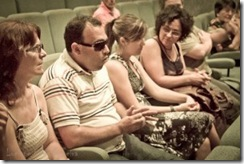 Pessoas sentadas em um auditório, cegos em destaque