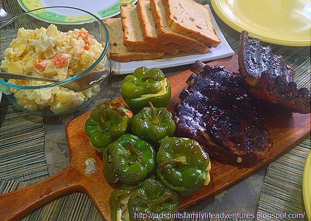 Baby back ribs served with potato salad and baked stuffed green bell pepper