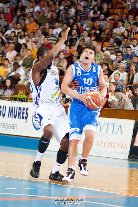 Adrian Tudor (albastru) incearca sa treaca de Mike James, in meciul dintre CSU Asesoft Ploiesti si BC Mures Tirgu Mures din cadrul turneului amical Mures Cup, disputat joi, 8 septembrie 2011 in Sala Sporturilor din Tirgu Mures