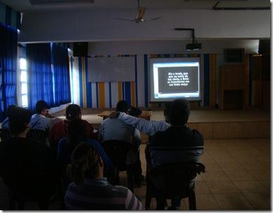 Cinema com audiodescrição: pPessoas em uma sala de aula assistindo a um filme