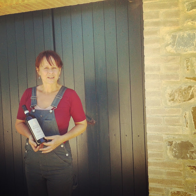 A vineyard worker holding a bottle of Brunello di Montalcino