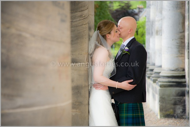 Bride and groom at the pillars of dollar academy scotland