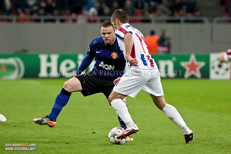 Sorin Frunza (11) incearca sa treaca de Wayne Rooney (10) in timpul meciului dintre FC Otelul Galati si Manchester United din cadrul UEFA Champions League disputat marti, 18 octombrie 2011 pe Arena Nationala din Bucuresti.