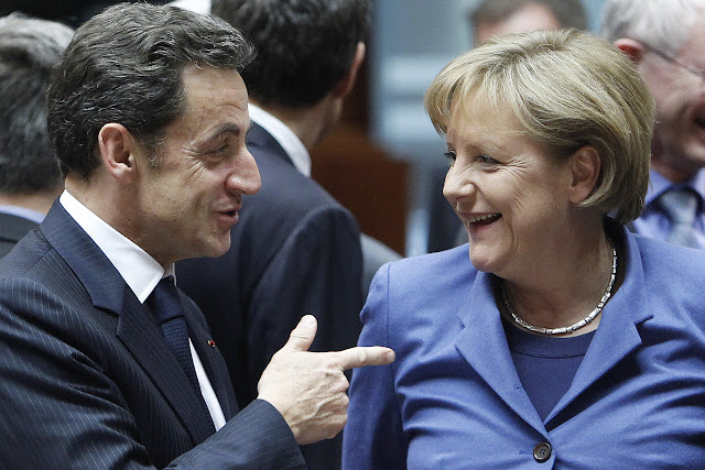 France's President Nicolas Sarkozy (L) talks with German Chancellor Angela Merkel at the start of a European Union leaders summit in Brussels March 25, 2010. France and Germany have reached a deal on a financing plan for crisis-hit Greece that will involve EU member states and the International Monetary Fund, the Elysee said on Thursday.  REUTERS/Yves Herman   (BELGIUM - Tags: POLITICS BUSINESS IMAGES OF THE DAY)