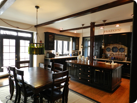 black cabinets wood beams kitchen