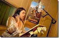 Mulher em uma cabine, com fones de ouvido e falando ao microfone. Atrás dela, o cartaz de um filme pendurado em uma parede