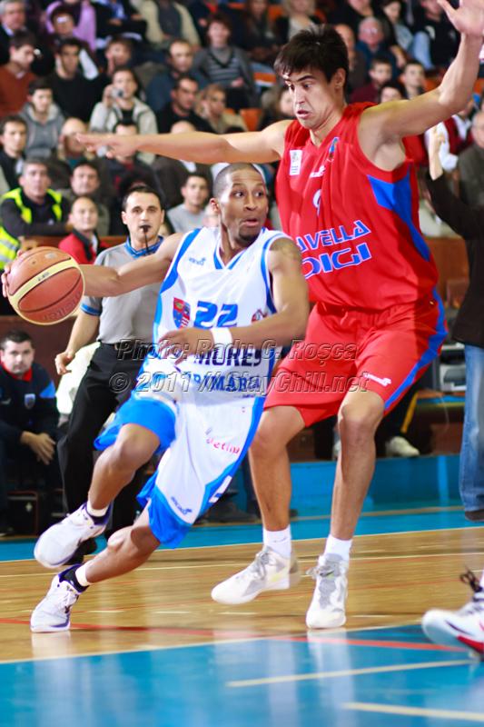 JuJuan Cooley incearca sa treaca de Milos Pesic  in timpul meciului de baschet dintre BC Mures si CSM Oradea disputat in Sala Sporturilor din Tirgu Mures din data de 29 octombrie 2011.