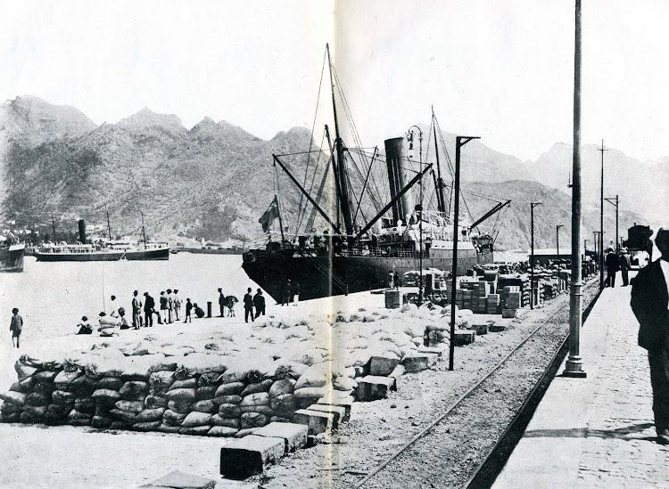 En esta foto se aprecia, detras del vapor ingles atracado, la silueta del ATLANTE fondeado en Tenerife. Del LIBRO DE INFORMACION PARA EL PASAJERO. CIA TRASATLANTICA. AÑOS 1913-1914.jpg