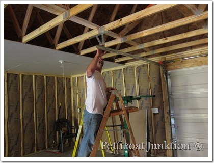 Jay hanging drywall in the Owen Workshop Petticoat Junktion