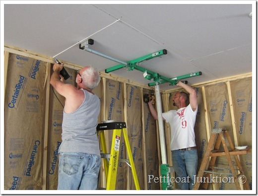 Dad and son working together hanging sheetrock