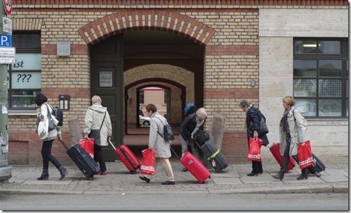 Menschen mit roten Rollkoffern in der Torstraße