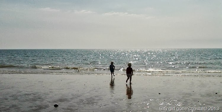 two boys running out to sea