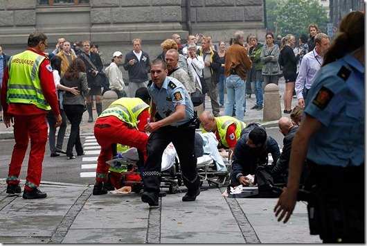 Injured people are treated by medics at the scene of an explosion near the government buildings in Norway's capital Oslo on July 22, 2011. At least one person was killed by the powerful explosion which ripped through government and media buildings. AFP PHOTO / SCANPIX / BERIT ROALD   -- NORWAY OUT -- (Photo credit should read ROALD, BERIT/AFP/Getty Images)