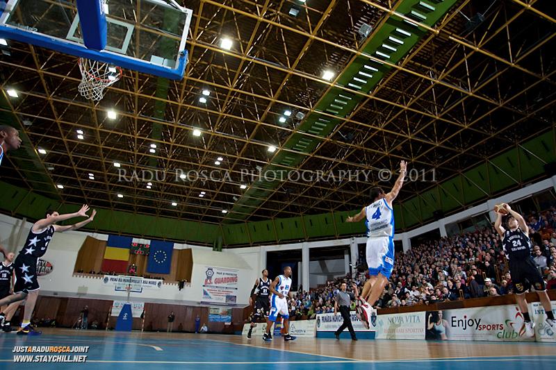 Tyler Morris incearca sa inscrie de la 3 puncte in timpul  partidei dintre BC Mures Tirgu Mures si U Mobitelco Cluj-Napoca din cadrul etapei a sasea la baschet masculin, disputat in data de 3 noiembrie 2011 in Sala Sporturilor din Tirgu Mures.