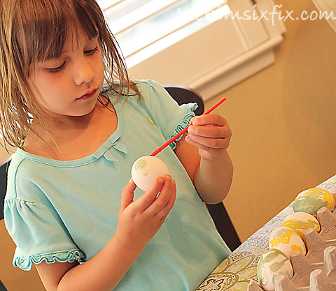 Child painting easter egg