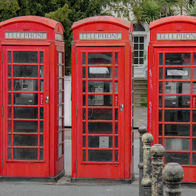 Three  red phone booths, England by Judith Dueck - City,  Street & Park  Street Scenes ( nobody, old, phone, street, travel, historic, city, monochromatic, empty, three, payphone, eastbourne, symbol, global, tourism, phonebox, booth, landmark, tourist, european, london, phonebooth, scene, antique, english, kiosk, culture, famous, call, europe, retro, england, telecommunications, typical, kingdom, pay, classic, uk, united, vintage, british, communication, traditional, history, urban, red, great, victorian, box, public, telephone, britain )