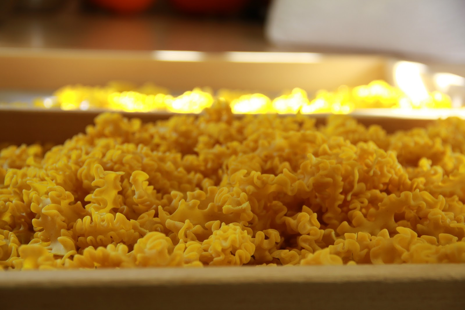 Du siehst ein Tablett voller gekringelter Nudeln, die in der Nudelmanufaktur Morlock Bad Teinach Zavelstein hergestellt werden.
