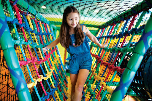 Norwegian-Cruise-Line-Splash-Academy-climbing-girl - Kids can cross a colorful bridge, enter tunnels and stay entertained in Splash Academy aboard your Norwegian Cruise Line sailing.