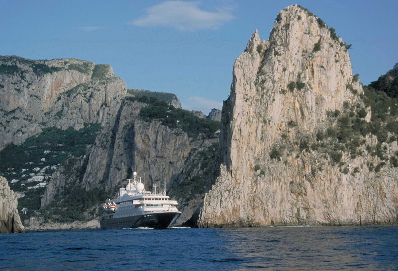 A SeaDream ship sails past a dramatic cliffscape in Capri, Italy.