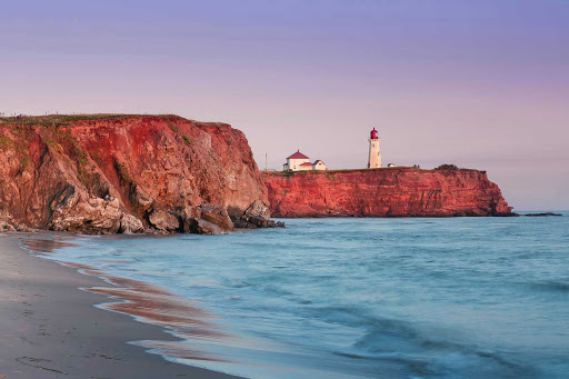 Havre-Aubert-lighthouse-Quebec - Red cliffs sit beneath the Havre-Aubert lighthouse on Iles De La Madeleine. The Magdalen Islands form a small archipelago smack in the middle of the Gulf of Saint Lawrence, Canada.