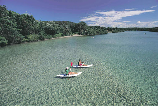 Kayakers paddle through turquoise waters at South West Rocks, Kempsey, North Coast NSW, Australia.